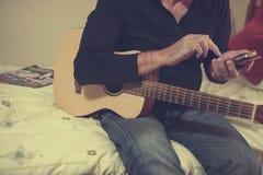 Mens met gitaar en telefoon stock foto