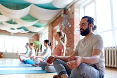 Mens met groep die mensen bij yogastudio mediteren stock fotografie