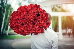 mens met groot boeket van rozen openlucht Royalty-vrije Stock Fotografie