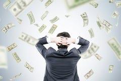Mens met handen achter hoofd en dollars het vallen Stock Afbeelding