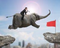 Mens met het gebruiken van spreker het berijden olifant die naar rode vlag vliegen Stock Foto