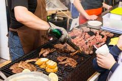 Mens met het Koken van Vlees bij de Grill bij Voedselfestival royalty-vrije stock fotografie