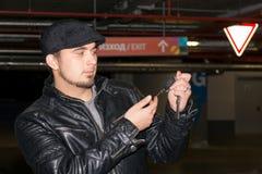 Mens met hoedenholding in zijn sleutel van de handauto Royalty-vrije Stock Afbeelding