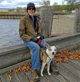 Mens met hond, die op een dok zitten stock foto
