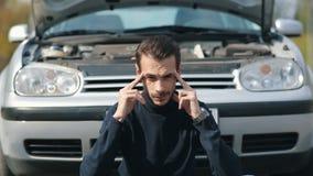 Mens met hoofdpijn in een voorzijde van gebroken auto stock videobeelden
