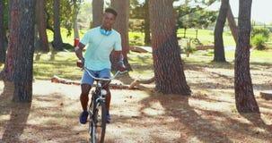 Mens met hoofdtelefoons die fiets in het park 4k berijden stock video