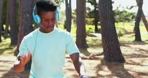 Mens met hoofdtelefoons die fiets in het park 4k berijden stock videobeelden
