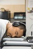 Mens met hoofdtelefoons die op laptop slapen. Stock Afbeelding
