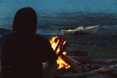 Mens met kajak dichtbij kampvuur op het strand in de avond stock fotografie