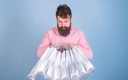 Mens met in kapsel en baard die zilveren zakken houden Hipster in roze overhemd met nieuwsgierige die blik op blauw wordt geïsole stock fotografie