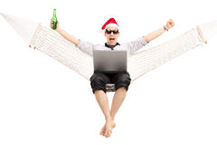 Mens met Kerstmanhoed die aan laptop in een hangmat werken Stock Foto's
