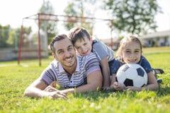 Mens met kind speelvoetbal op gebied stock fotografie