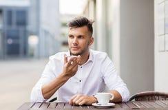 Mens met koffie en smartphone bij stadskoffie Stock Afbeelding