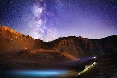 Mens met koplamp in de bergen bij nachthemel royalty-vrije stock foto's
