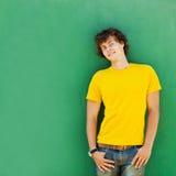 Mens met krullend haar in een gele T-shirt Stock Foto