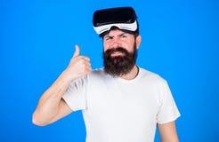 Mens met lange baard en ernstig gezicht die O.K. gebaar tonen Hipster met in baard die VR-digitale beschermende brillen dragen, Stock Foto