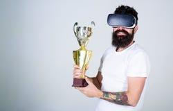 Mens met lange baard gelukkig over zijn overwinning in online spelentoernooien, gokkenconcept Vrolijke gebaarde kampioen stock foto's