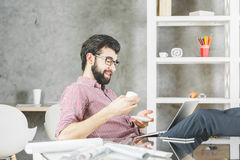 Mens met laptop het drinken koffie Royalty-vrije Stock Afbeeldingen