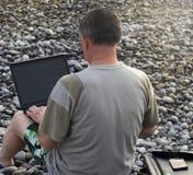Mens met laptop op het strand stock foto