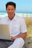 Mens met laptop op strand Stock Afbeelding