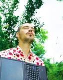 Mens met laptop in tuin stock afbeelding