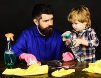 Mens met leuk kind op zwarte Jong geitje en vader met bezige gezichten die samen met nevel schoonmaken Ouders weinig helperconcep stock foto