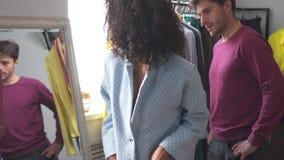 Mens met meisje het proberen op kleding bij boutique stock video