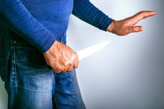 Mens met mes en hand bij gebaar van verzoening Conflictgeweld royalty-vrije stock afbeelding