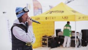 Mens met microfoon onder snowboarders en skiërs bij de skitoevlucht Gele tent stock footage