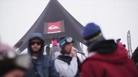 Mens met microfoon onder snowboarders en skiërs bij de skitoevlucht Rooksigaret stock footage