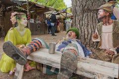 Mens met middeleeuws kostuum die simulerend dronkenschap liggen stock fotografie