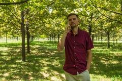 Mens met mobiele telefoon in de zomerpark Jonge knappe mens met sm Royalty-vrije Stock Fotografie