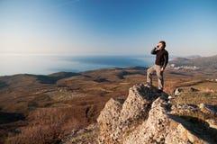 Mens met mobiele telefoon op de bovenkant van wereld Stock Fotografie