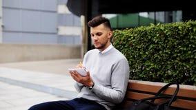 Mens met notitieboekje of agenda die op stadsstraat schrijven stock videobeelden
