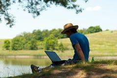 Mens met notitieboekje op riverbank Royalty-vrije Stock Afbeeldingen