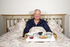 Mens met Ontbijt in Bed Royalty-vrije Stock Afbeeldingen