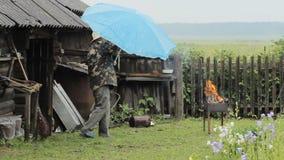 Mens met paraplu dichtbij de brand voor barbecue De regen valt, een oud gebouw met een omheining op de achtergrond stock footage