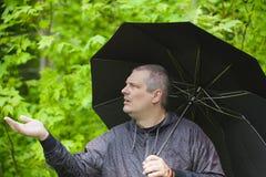 Mens met paraplu in park Royalty-vrije Stock Afbeeldingen