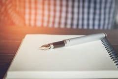 Mens met pen op notitieboekje Stock Afbeeldingen