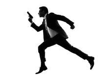 Mens met pistool lopend silhouet Stock Foto's