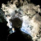 Mens met rook tegen donkere achtergrond wordt gesilhouetteerd die royalty-vrije stock foto