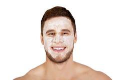 Mens met roomvochtinbrengende crème op zijn gezicht Stock Foto's