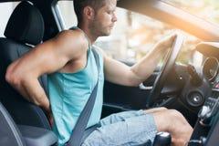 Mens met rugpijn na een lange aandrijving in auto stock afbeeldingen
