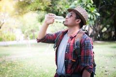 Mens met rugzak drinkwater van fles in bos stock foto's