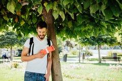 Mens met rugzak en een gift naast een boom stock afbeelding