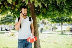 Mens met rugzak en een gift naast een boom royalty-vrije stock foto