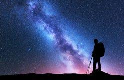 Mens met rugzak en trekkingspolen tegen Melkweg stock fotografie