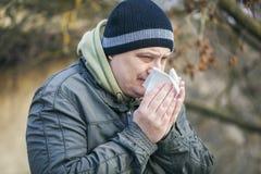 Mens met servet dichtbij neus bij in openlucht op de bank Stock Foto's