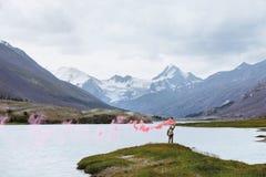 Mens met signaalbrand op achtergrond van bergmeer royalty-vrije stock fotografie
