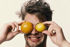 Mens met sinaasappel en citroen in plaats van ogen in handen Royalty-vrije Stock Afbeeldingen